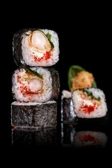 검은 배경에 후토 마키를 굴립니다. 스시 메뉴. 일본 음식.