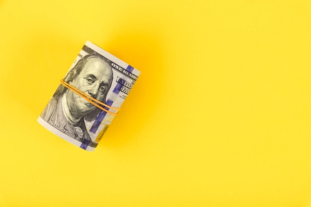 A roll of hundred dollar american bills is tied with an elastic band on a yellow background