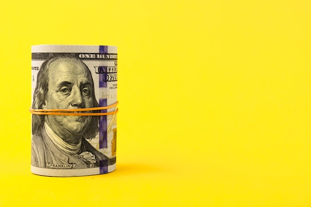 A roll of hundred-dollar american bills is tied with elastic band on a yellow