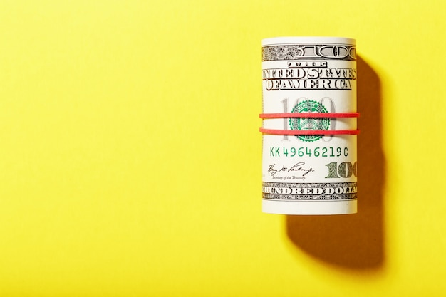 A roll of hundred-dollar american bills is tied with a red elastic band on a yellow background.