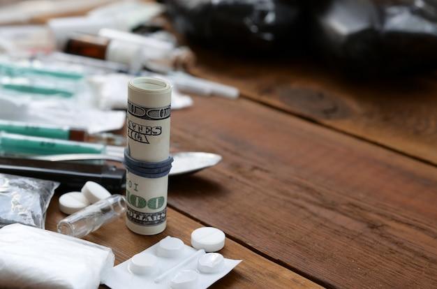 Roll of hundred dollar bills with narcotic drug dealer stuff