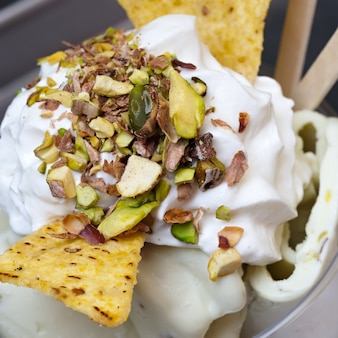 Roll ice cream is made by hand on the freezer sweet dessert made with  ground nuts of pistachios