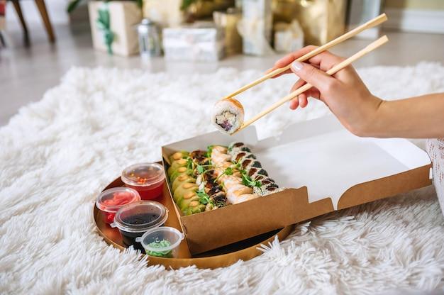寿司の入ったお盆を背景に女の子の手を転がします。