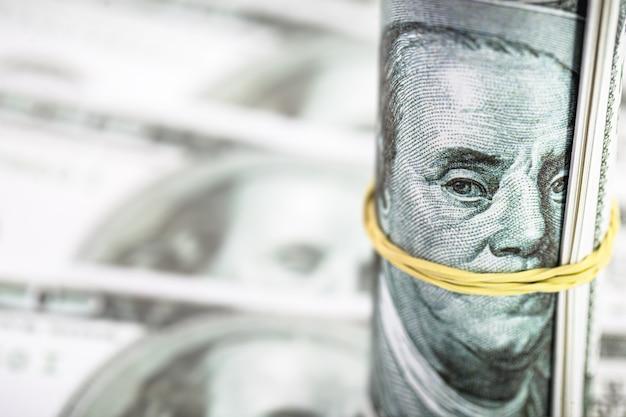 Рулон банкнот 100 американских долларов, на котором можно увидеть изображение президента бенджамина франклина с перевязанным резинкой ртом.
