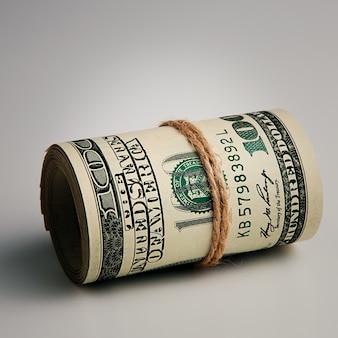 Рулон крупным планом сто американских долларов на серой поверхности. крупный план, свободное место для подписей и текста.