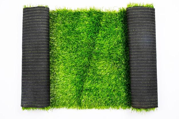 흰색 배경, 잔디, 운동장을 덮고 있는 인공 녹색 잔디 롤.