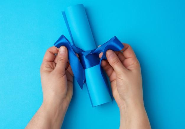Рулон синей бумаги, перевязанный шелковой синей лентой