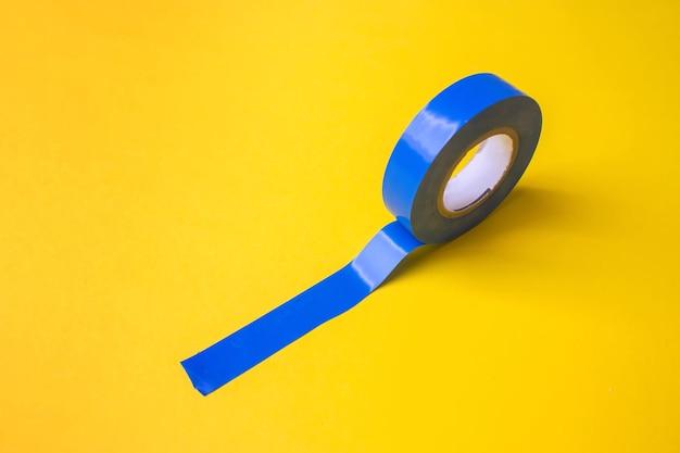 Рулон синей пластиковой клейкой ленты на желтом фоне. закройте вверх.