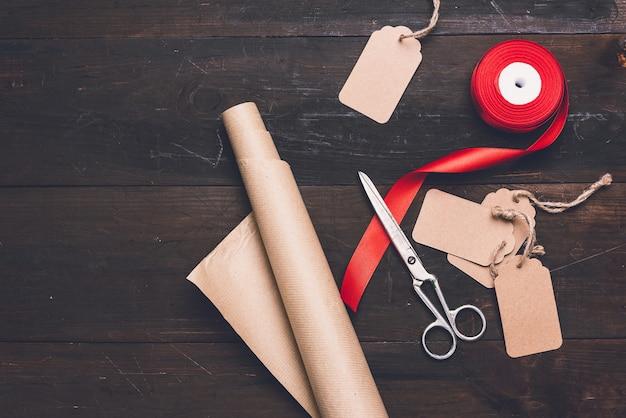茶色のクラフト包装紙のロール、赤い絹のリボン