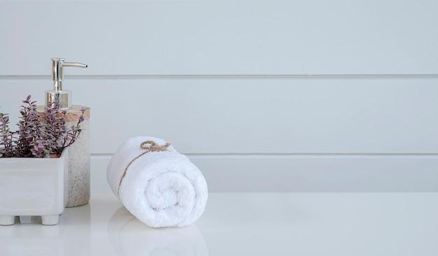 Рулон чистых спа-полотенец на белом столе с копией пространства.