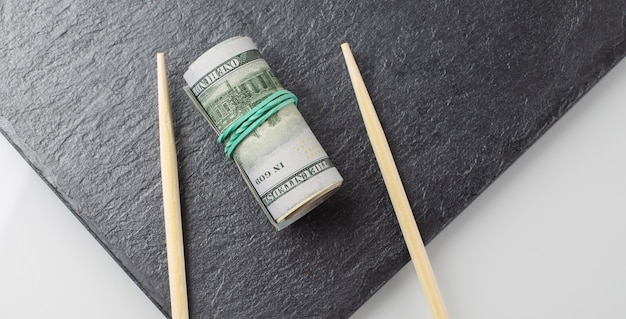Рулон долларов на черной тарелке на белом фоне