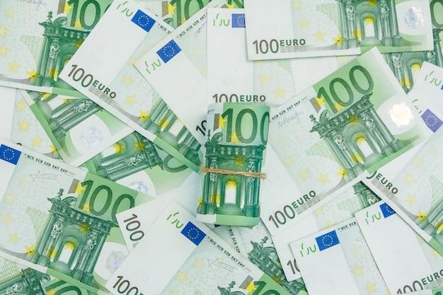 ユーロ紙幣のロール、100ユーロの多くの紙幣、欧州通貨の背景