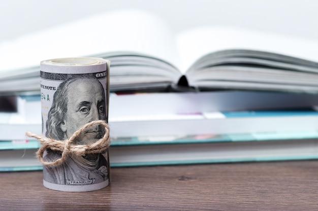 Рулон денег на фоне книг, оплата литературной работы
