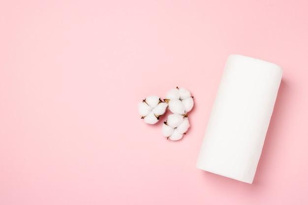 ピンクの背景にペーパータオルと綿の花のロール。コンセプトは100%ナチュラルな商品で、繊細でソフトです。フラット横たわっていた、トップビュー