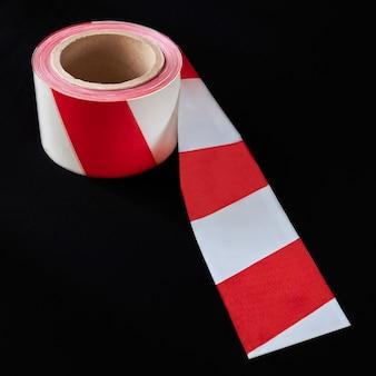 Рулон красно-белой ленты с предупреждением