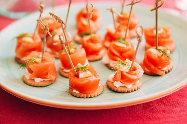 Рулет из красной рыбы на вертеле. филе лосося с укропом и лимоном. тарелка с маленькими бутербродами