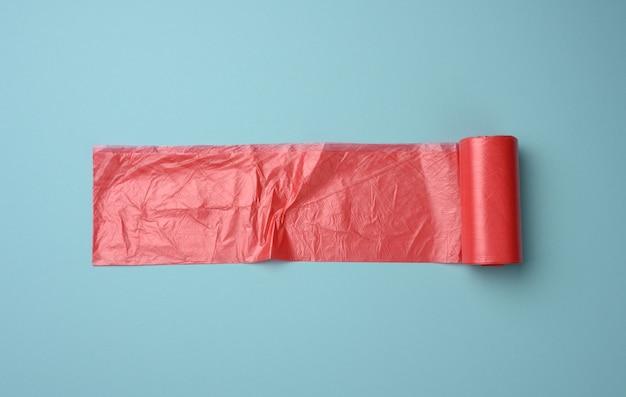 Рулон красных прозрачных пластиковых пакетов для мусорного ведра на синем фоне, вид сверху