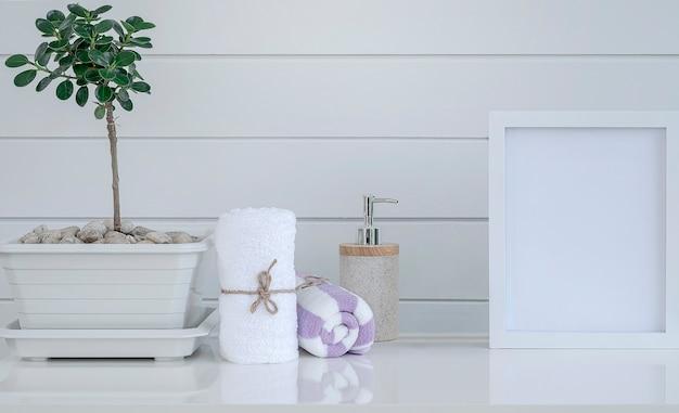 Рулон спа-полотенец, бутылки с мылом и деревянной рамы на белом столе с белой деревянной стеной.