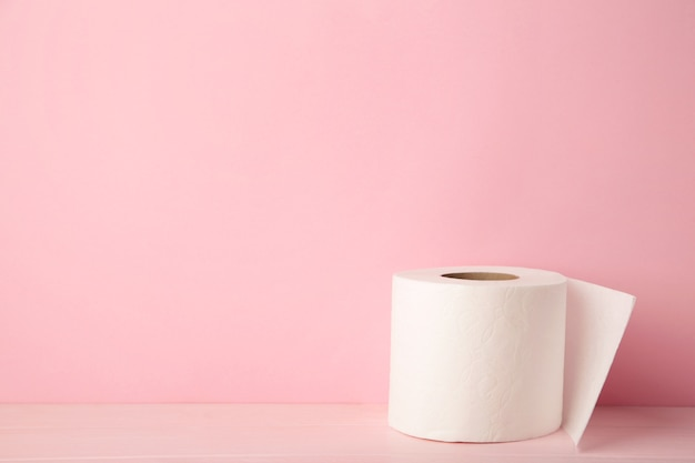 Рулон туалетной бумаги на розовом фоне