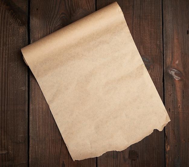 Рулон раскрученной оберточной бумаги на деревянной поверхности из старых досок