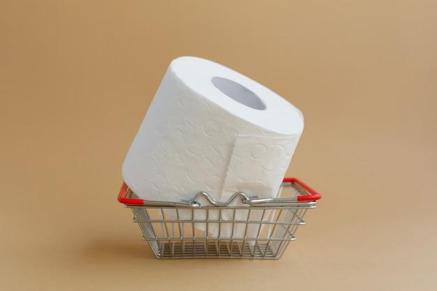 Рулон белой туалетной бумаги на коричневом фоне и корзина с продуктами