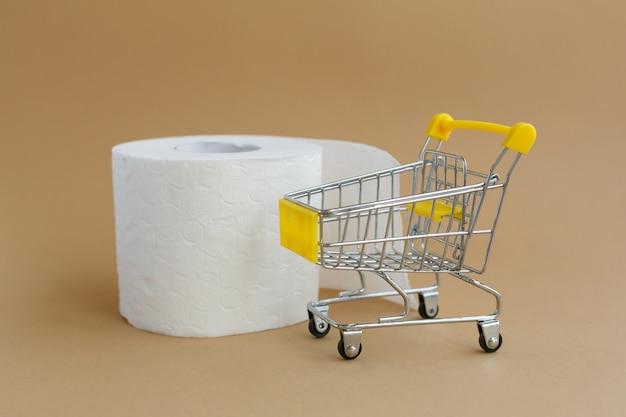 Рулон белой туалетной бумаги с рукавом с рисунком или перфорацией и продуктовая тележка на коричневой поверхности