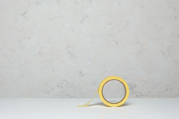 Рулон желтой бумажной маскировочной ленты на деревянный стол