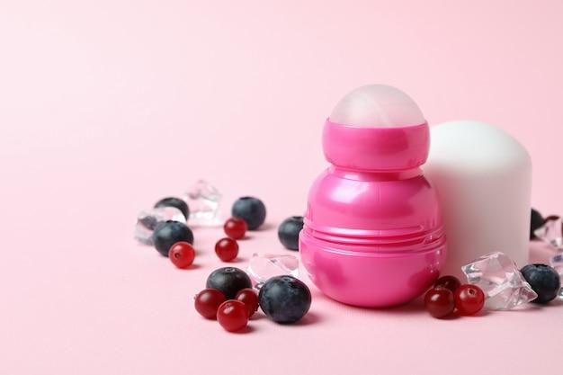 롤온 탈취제, 얼음 조각 및 딸기 분홍색 배경