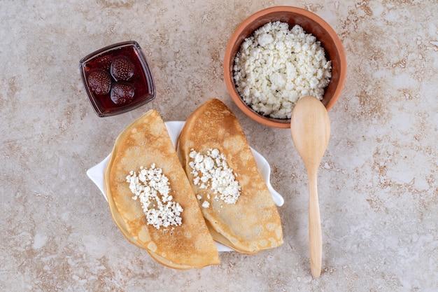 Arrotolare le frittelle con ricotta e marmellata di fragole