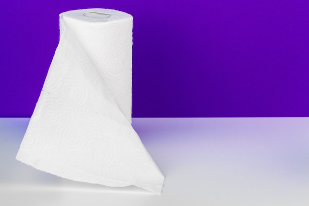 Roll of paper towel on table against purple
