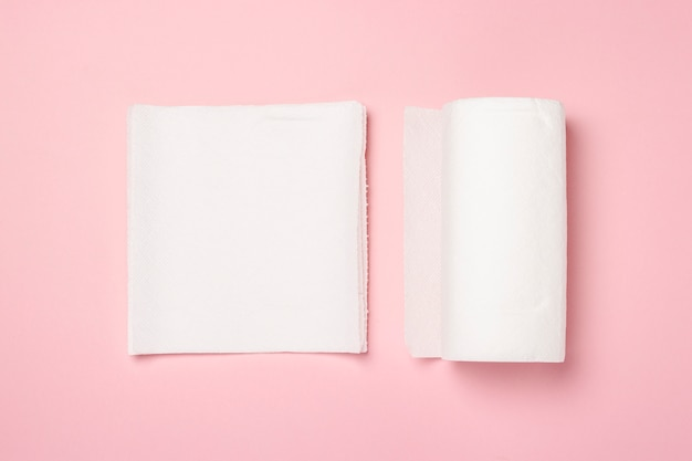 Roll of paper towels and few pieces towels on a pink surface. concept is 100 natural product, delicate and soft. flat lay, top view.