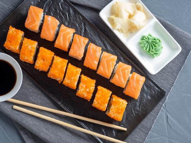 フィラデルフィアとカリフォルニアを黒いプレートに転がします。上面図、フラットレイ。生姜、わさび、醤油が近くにあります。伝統的な日本料理