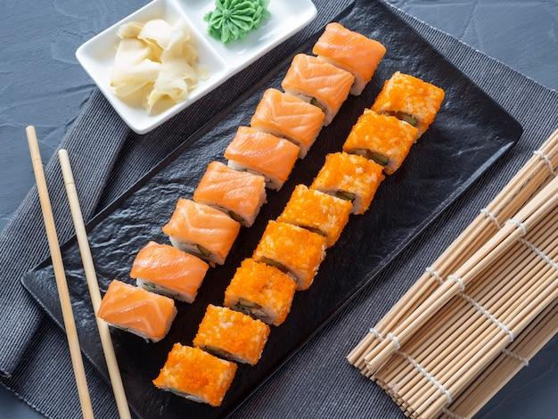 フィラデルフィアとカリフォルニアを黒いプレートに転がします。上面図、フラットレイ。生姜、わさび近く。伝統的な日本料理