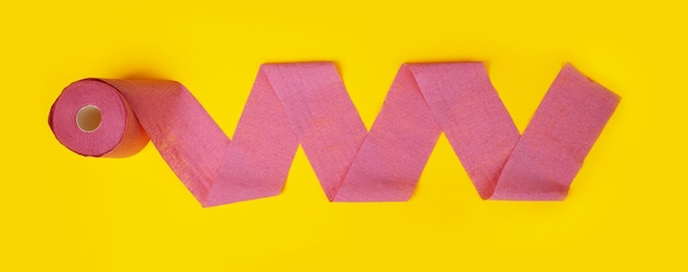 Roll of pink toilet paper over yellow background, panoramic image