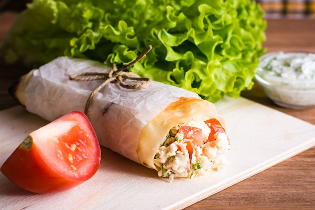 Roll of pita with filling, tomato, lettuce and sauce on a wood table