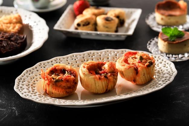 Рулет из хлеба для пиццы с сыром моцарелла, колбасой, петрушкой в белой керамической тарелке на черном мраморном фоне