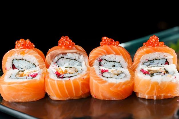 연어, 레드 캐비어, 토비코, 장어, 쌀, 노리 클로즈업으로 레드 드래곤을 굴립니다. 스시 전통적인 일본 요리입니다.