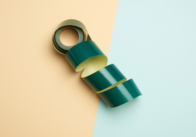 Roll of rolled paper sticky tape on colored background