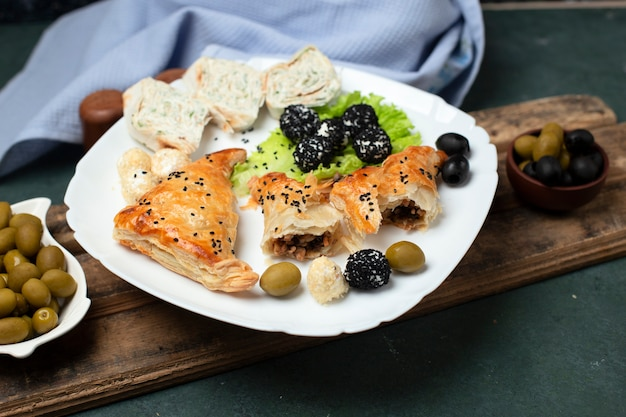 Roll salad with pastry and olives in a white plate
