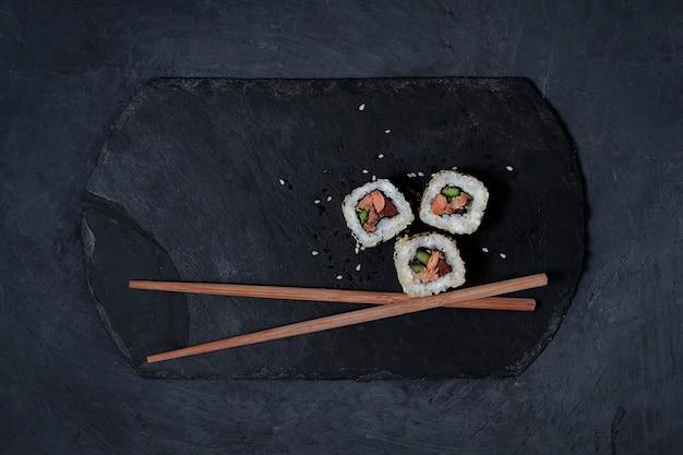 Ролл с лососем терияки, на черном камне, вид сверху, без людей, горизонтальный. фото высокого качества