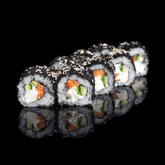 Roll smoked california with cucumber, avocado, eel and black tobiko caviar on black with reflection. close up. japanese cuisine. photo for menu