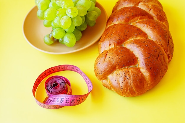 Roll of tape measure, grapes and bun with poppy seeds on a yellow background