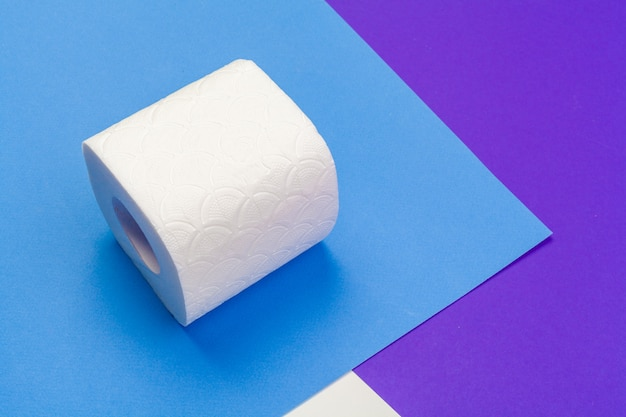 Roll of toilet paper on blue color background