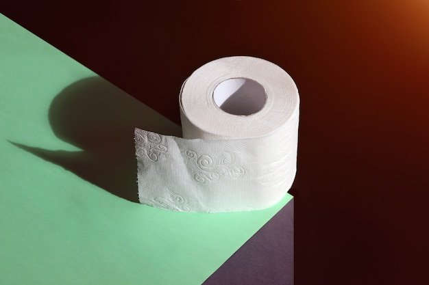 Roll of toilet paper on edge concept for sale and necessity on dark background