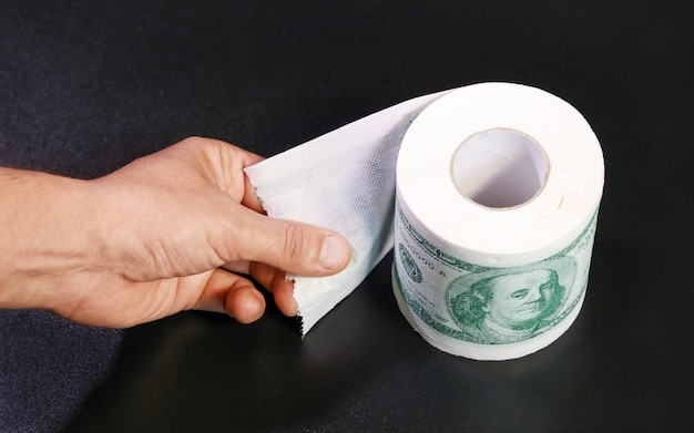 Roll of toilet paper in form of dollars hand holds unlocked edge