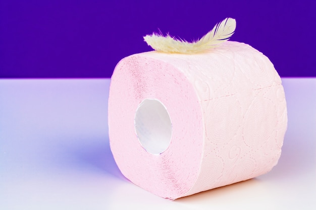Roll of toilet paper and soft feather on color table
