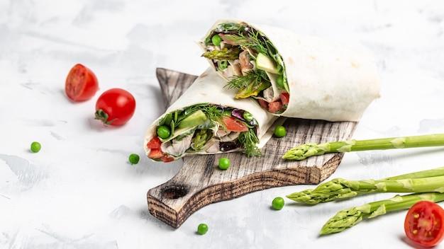 アスパラガス、アボカド、トマト、エンドウ豆、チーズ、タルタルを添えたチキンフィレのグリルでトルティーヤをロールパン
