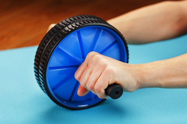 Roll for training the press in the hands on a blue rug.