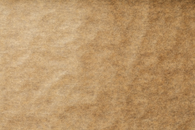 A roll of unfolded brown parchment paper, for baking food in background, top view.