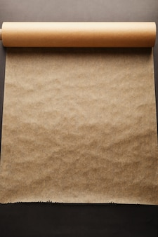 A roll of unfolded brown parchment paper for baking food in on dark